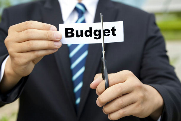 man in business suit cutting budget sign in half